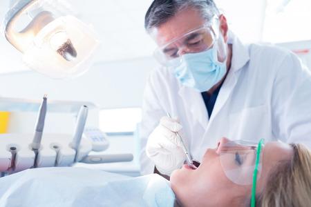dentista: Dentista que examina a los pacientes dientes en la silla de los dentistas en la cl�nica dental