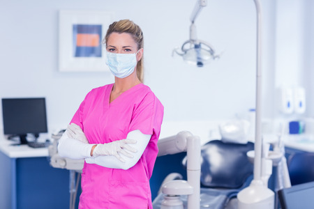 Dentist in pink scrubs looking at camera with arms crossed at the dental clinic Stock Photo