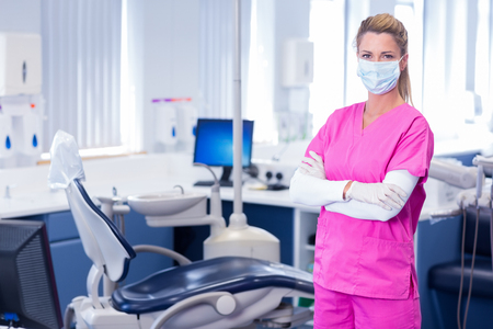 Dentist in surgical mask standing with arms crossed at dental clinic