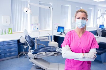 歯科医院で腕を突っ立っているサージカル マスクで歯科医が折り畳まれて