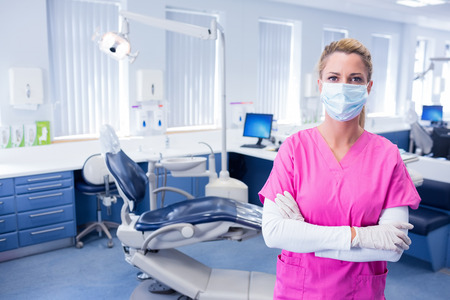 Zahnarzt in chirurgische Maske stand mit der Waffe in der Zahnklinik gefaltet Standard-Bild - 36418481