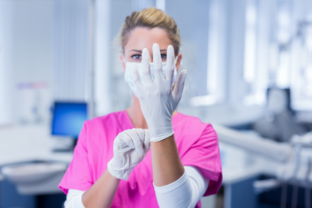 surgical gloves: Dentist in pink scrubs putting on surgical gloves at the dental clinic Stock Photo