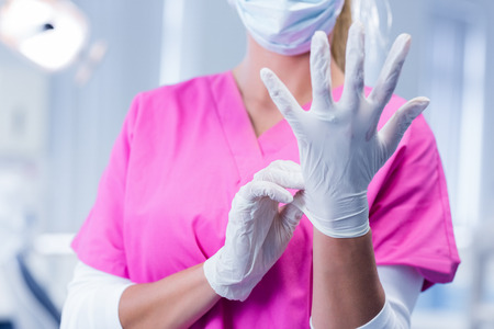 putting on: Dentist in pink scrubs putting on surgical gloves at the dental clinic Stock Photo
