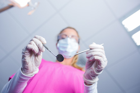 surgical mask: Dentist in surgical mask holding tools over patient at the dental clinic Stock Photo