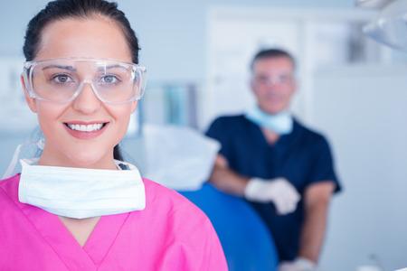 Lachende assistent met beschermende glazen bij de tandheelkundige kliniek