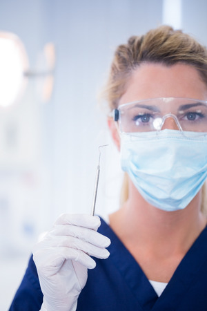 surgical mask woman: Dentist in mask holding dental explorer at the dental clinic