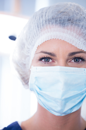 surgical mask: Dentist in surgical mask and cap looking at camera at the dental clinic
