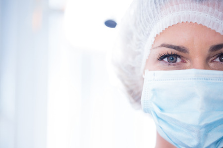 surgical mask woman: Dentist in surgical mask and cap looking at camera at the dental clinic