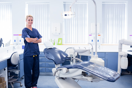 Dentist in blue scrubs standing with arms crossed beside chair at the dental clinic Foto de archivo
