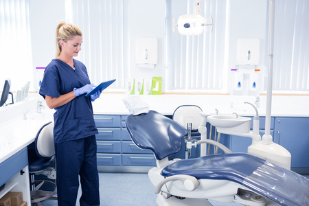 Dentist working on tablet pc at the dental clinic Stock Photo