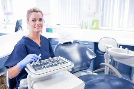 mid adult   female: Dentist sitting with tray of tools smiling at camera at the dental clinic