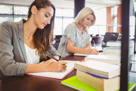 matures: Matures females students writing notes at desk in library