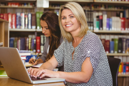 revision book: Smiling mature female students using her laptop in library