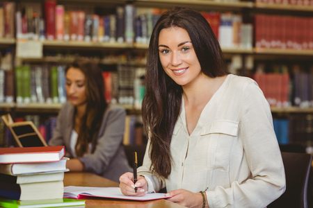 college student: Smiling pretty brunette student writing in notepad in library