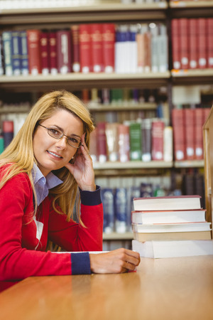 revision book: Smiling mature student studying at desk in library Stock Photo
