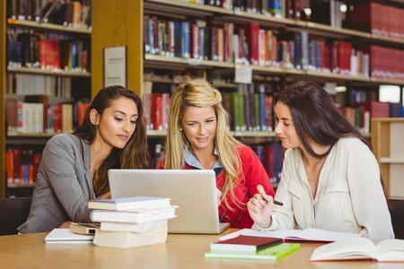 classmates: Smiling mature student with classmates using laptop in library Stock Photo