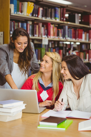revision book: Pretty student showing her classmates something on laptop in library