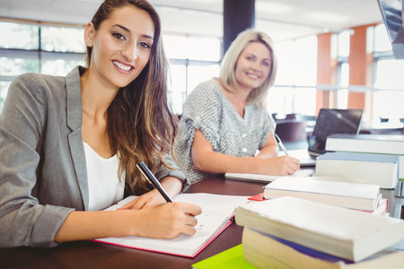 revision book: Smiling matures females students writing notes at desk in library