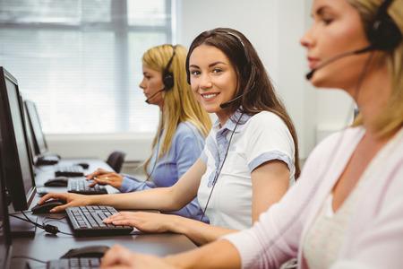 servicio al cliente: Agente sonriente del centro de atenci�n telef�nica que habla en el auricular en la oficina