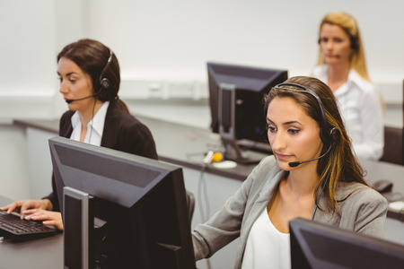 center agent: Call centre agents talking on the headset in the office