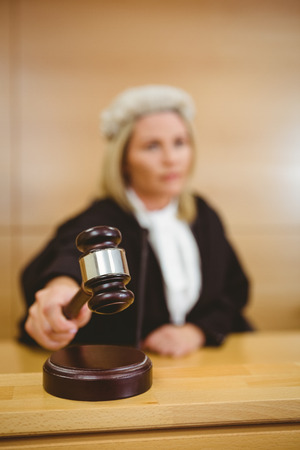 court room: Serious judge with a gavel wearing robes and wig in the court room