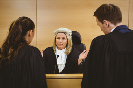 trial indoor: Judge wearing a dress and a wig speaking with lawyers in the court room Stock Photo