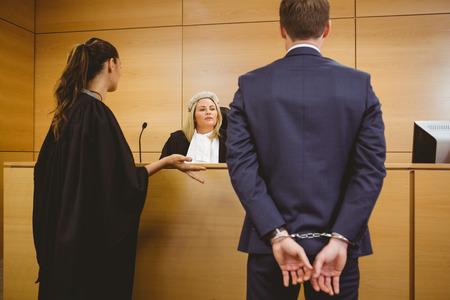 mandato judicial: Juez de hablar con el criminal esposado en la sala del tribunal Foto de archivo