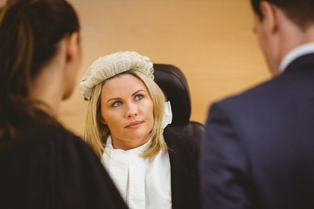 courtroom: Judge and lawyer listening the criminal in handcuffs in the court room