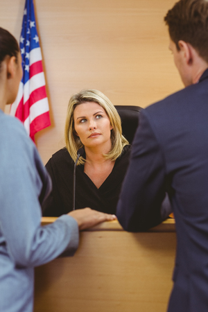 trial indoor: Judge and lawyers speaking in front of the american flag in the court room