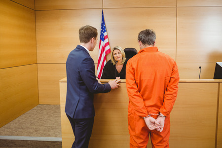 Lawyer and judge speaking next to the criminal in handcuffs in the court room photo
