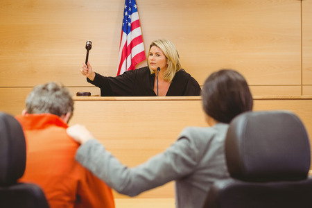 Judge about to bang gavel on sounding block in the court room photo