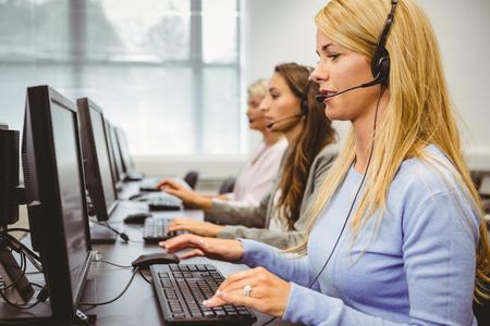 servicio al cliente: Los agentes del centro de llamadas hablando por el auricular en la oficina