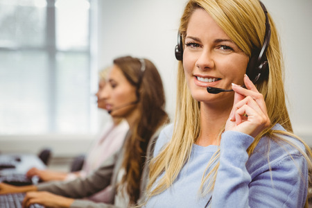 center agent: Smiling call centre agent talking on the headset in the office Stock Photo