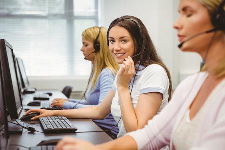 centro de computo: Agente sonriente del centro de atenci�n telef�nica que habla en el auricular en la oficina