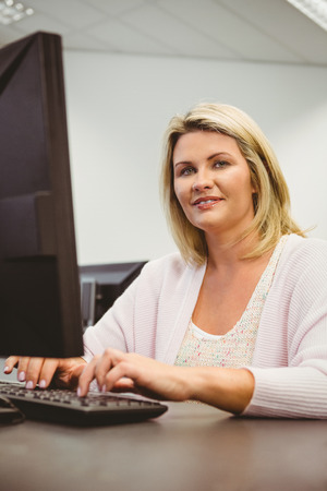 mature student: Mature student using laptop looking at camera in the office Stock Photo