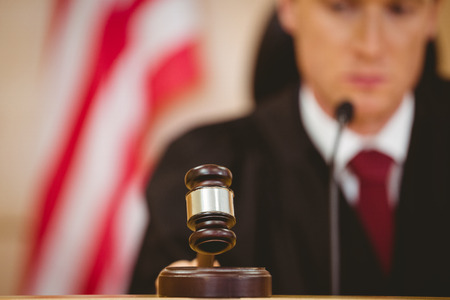 young adult men: Stern judge about to bang gavel on sounding block in the court room