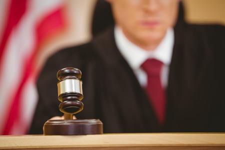 orden judicial: Juez serio a punto de golpear el martillo en el bloque de sonar en la sala del tribunal