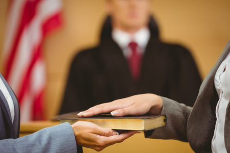 Witness swearing on the bible telling the truth in the court room Foto de archivo