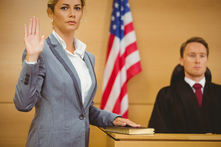 female judge: Witness swearing on the bible telling the truth in the court room Stock Photo