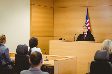 courtroom: Unsmiling judge with american flag behind him in the court room