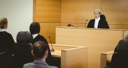 Sans sourire juge portant perruque avec drapeau américain derrière lui dans la salle d'audience