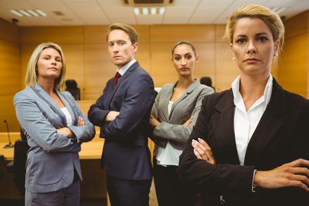 腕を組んで裁判所の部屋に立っている seu は弁護士