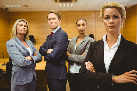 female lawyer: Serious lawyer standing with arms crossed in the court room