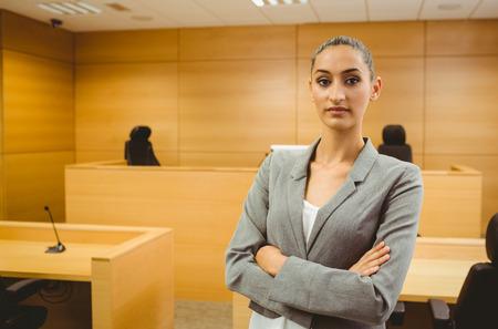 mandato judicial: Abogado Sin sonre�r mirando a la c�mara cruz� los brazos en la sala del tribunal Foto de archivo