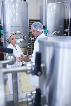 biologist: Biologist team talking and wearing hairnet in the factory