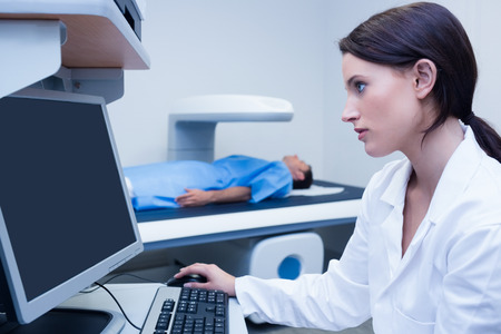 proceeding: Doctor looking her computer while proceeding a radiography in hospital