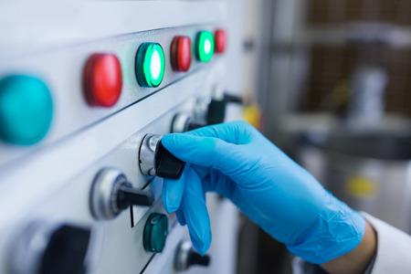 maquinaria: Mano con guantes girando botones de la m�quina en la f�brica