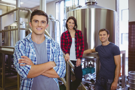 microbrewery: Casual happy stylish team smiling at camera together in the factory Stock Photo