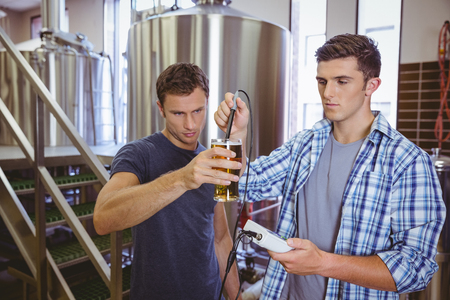 casual men: Two casual men testing beer in the factory Stock Photo