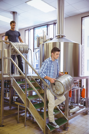 microbrewery: Young men carrying keg smiling at camera in the factory Stock Photo